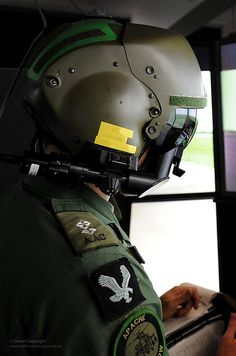 An Apache helicopter pilot concentrates on simulator screens during training.