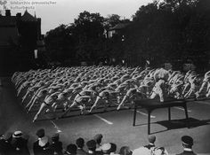 Performing Calisthenics at a Gymnastics Festival (June 6-9, 1911)   This photograph by the Haeckel brothers shows athletes performing calisthenics at a gymnastics festival in Gotha (Thuringia) in which teams from various universities took part. In Germany, clubs and societies came together around various interests, including gymnastics. Public sports and gymnastics festivals, such as the one shown here, created a sense of community and solidarity among participants.