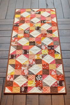 fall table runner - Kitchen Table Quilting. Cheyenne quilt block. There is no pattern, but it is a four patch block with half square triangles with the same colored background fabric.