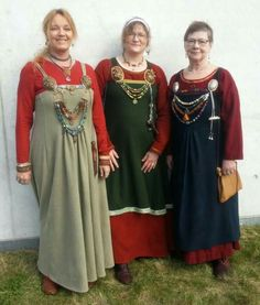 Pleated apron dress far last and far right. Note placement of pleats.