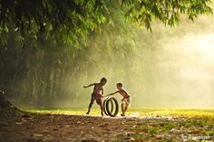 """Hey don't cheat, it's my tire! indonesian children from rural area, playing a """"tire race"""" these children can have fun even with a simple stuff, it's not about the toy it's about the joy :D Jorge Arias, Village Photography, Dont Cheat, Earth Song, Arte Tribal, Street Portrait, Traditional Games, Beautiful Children, Creative Photography"""