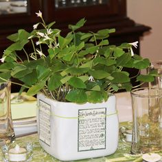 Square white vase/planter, printed Irish Blessing or Irish Motif wiht hole punches at top: string, wrap and tie. Table Decor for St. Patrick's Day - Interiors by Patti Blog - INTERIORS BY PATTI