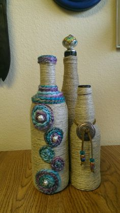 Another wine bottle. I wrapped it with waxed hemp and used scrap yarn to embellish. The short bottle is a beer bottle.