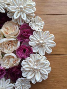 布を小さく切って折りたたみ花びらを作る伝統工芸のつまみ細工です。シルク布を使って清楚で上品な花を周りにあしらい、中心にはミニバラのフェイクフラワーを飾ったリー...|ハンドメイド、手作り、手仕事品の通販・販売・購入ならCreema。