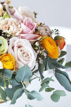 Delikat uttrykk med ranunkler, roser og nelliker i pastellfarger.