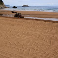 Stars printed in sand by tractor as it drags giant roller across beach-Swedish Artist Gunilla Klingberg