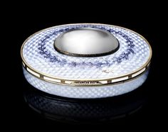 A jewelled enamel and silver-gilt pillbox by Fabergé with Imperial Warrant, Moscow, 1899-1908, the oval hinged box enamelled pale translucent lilac over wavy engine turning, the lid centred with cabochon moonstone within dentritic surround, opening at hinged lid with diamond-set thumb piece further enriched with opaque sections at intervals to border to reveal gilt interior. Provenance: Collection of Robert Gascoyne-Cecil, 6th Marquess of Salisbury.