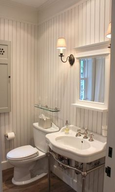 Inn at Little Pond - Beautiful cottage bathroom features white beadboard backsplash framing framed mirror with shelf flanked by oil-rubbed bronze quatrefoil sconces over 2-leg washstand accented with vintage style faucet next to vintage glass shelf over toilet.