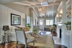 Contemporary Living Room with Carpet, Wall sconce, Hardwood floors, Cathedral ceiling, Cement fireplace, Exposed beam