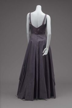 Evening dress 1940 Evening dress of navy blue silk. Bodice with narrow straps over the shoulders. Long skirt flared form the waist, with wide ruffle applied low at side-backs and curving higher in front. At highest point of ruffle a silk bow and a cluster of five aritficial roses in pale pink and lavender are attached.