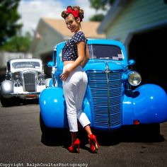 1950s style pinup girl in white capri pants poses in front of 1938 hot rod Chevy.