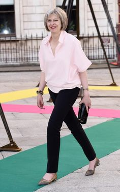 Theresa May wears a pink blouse with a black fitted trousers and leopard print…