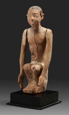 Homme assis. Statuette provenant d'un modèle représentant un homme vêtu d'un pagne blanc, assis, les bras le long du corps. Il est coiffé d'une perruque. Bois et traces de polychromie. Égypte, Moyen Empire.