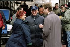 """Natalie Portman (left) and Jude Law (right) talk with director Mike Nichols (center) on the set of """"Closer"""", 2004."""