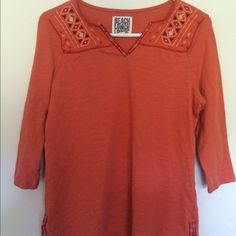 pale orange 3/4 sleeve cotton tunic flowing loosely cut embroidered tunic with slot hem at hip-adorned with ribbon detail. great melon color works well with jeans and accessories in many hues and shades. this is a small, but the cut is generous. love this top. Beach Lounge Lunch Tops Tunics