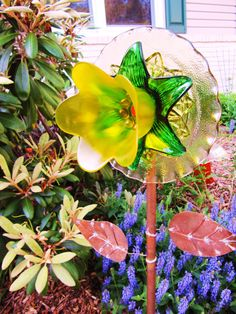 This piece was designed to stand on a stake in your garden or yard and serve as a sun-catcher, or garden ornament. Plate flowers are the a new trend in up-cycling, repurposing, vintage glass garden art! They are bonded together permanently, with an industrial strength glass bonding adhesive and do not come apart. This forever flower is yellow, and green, with a grouping of beads the center bead is red. It combines four pieces of vintage glass. It really does the job reflecting the light…