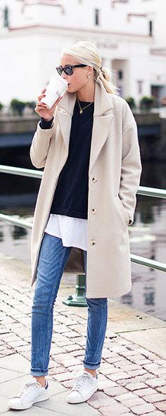 Ellen Claesson is wearing a coat, blue knit jumper from Filippa K, long white T-shirt from Acne, jeans from Zara and shoes from Adidas Stan Smiths