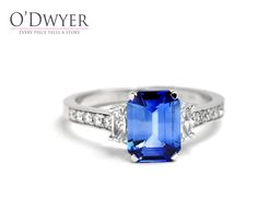 5th Avenue Ring - 18ct white gold ring with an emerald cut blue sapphire and small diamonds.