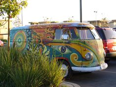Here is a trippy psychedelic VW Van painted with a lot of blue and yellow. It has a giant eye on the front door and a lot of cool patterns on the side of the bus. It has a marijuana leaf and water ...