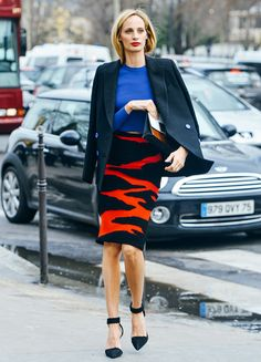 Lauren Santo Domingo stands out in a bright blue sweater, black and red printed skirt, and ankle strap heels