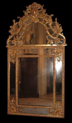 Very fine, French, Regence period mirror: In solid, carved giltwood with parcloses, having original giltwood surface and original mercury glass. Circa 1700.