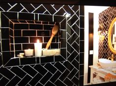 A recessed shelf for the shower in a contrasting tile pattern by Genevieve Gorder
