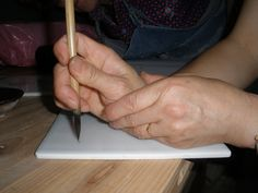 This is how the Chinese hold their brush to make fine detail. Go to webpage to get better picture.