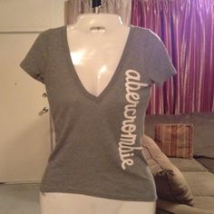 """Abercrombie & Fitch Top Abercrombie & Fitch V-Neck T-Shirt is made of 60% Cotton and 40% Polyester. Stylish and comfortable.  Size Medium. Color is Gray. Length """"22.5. Laying flat """"13.5. This item is in Good condition, Authentic and from a Smoke And Pet free home. All Offers through the offer button ONLY. I Will not negotiate Price in the comment section. Thank You😃 Abercrombie & Fitch Tops Tees - Short Sleeve"""