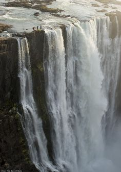 Steve Fisher, 37, Dale Jardine, 33, both from South Africa, and Sam Drevo, 33, from the U.S., paddled up to the lip of the mile-wide Victoria Falls - the largest waterfall in the world