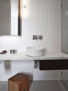 Rectangular white ceramic bathroom tile, staggered vertical installation, gray penny-round floors, marble counter