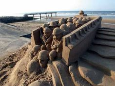 A sand sculpture of troops disembarking from a landing craft during the June D-Day invasion of the beaches of Normandy, France. Photo by Bernard Clerc-Renaud