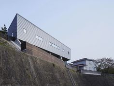 yo yamagata perches MS house atop steep incline.  At the client's request, the structure has a low profile in relation to surrounding properties. The concrete story is embedded within the terrain, with the lighter timber structure stacked on top. Steel beams allow the building to partially cantilever over the incline, with the upper level suspended five meters above the drop.  http://www.designboom.com/architecture/yo-yamagata-ms-house-shizuoka-japan-11-14-2014/