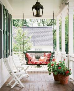 Hang a swing at one end of the porch and pile it with pillows for a cozy perch. Midwest Living