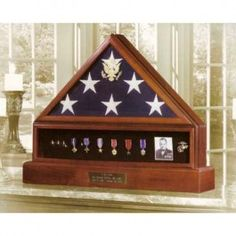The Presidential Pedestal Urn Flag & Medal Display Case is beautifully made of a Walnut Cherry blend and has an embossed Great Seal of the United States on the elegant beveled glass front.