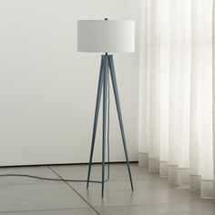 Shop Theo Blue Floor Lamp. Tall, trim, tapered tripod takes a stand in cool, understated teal-blue, topped by an ample linen drum shade that adds a classic note to the modern sculpture feel.