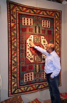 Hüseyin Konukcu in front of an antique Karachoph rug exhibited by Mirco Cattai Fine Arts & Antique Rugs.