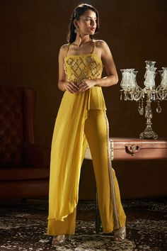 SANYA GULATI Featuring a mustard yellow pleated top in viscose crepe base with asymmetrical tassel detailing and noodle straps. It is paired with matching bell bottom pants having embroidery on the side seam. Indian Fashion Modern, Indian Fashion Designers, Indian Designer Outfits, Designer Party Wear Dresses, Kurti Designs Party Wear, Dress Indian Style, Indian Dresses, Indian Wedding Outfits, Indian Outfits