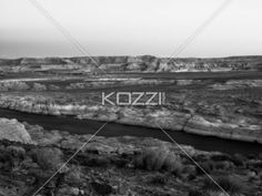 black and white image of mountain range with clear sky in background. - Black and white image of mountain range and river with clear sky in background.