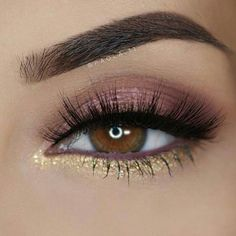Eyebrows are shaded in, eye shadow as a tan pink ish color, mascara and gold under the eye