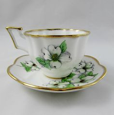 Stunning tea cup and saucer features large white flowers on the teacup and saucer. There is heavy gold trimming along the edges of the tea cup and saucer. Cup and saucer have a distinctive ruffled shape. Excellent condition (see photos). Markings read: Salisbury Fine Bone China Made in