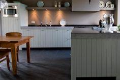 Een robuuste handgemaakte keuken met kleur. De fronten, van eikenhout en afgewerkt in een mooie Farrow en Balls kleur zorgen samen met de grote poten voor een robuuste uitstraling en geven de houten keuken kracht. Mooie grove lijnen sieren deze keuken met een natuurstenen werkeiland op houten poten.