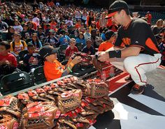 Buster Posey hands out gloves to Junior Giants kids on Wednesday, June 11, 2014. Buster donated 1,000 gloves to the Junior Giants.