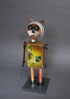 """Size: 17"""" tall by 5.5"""" wide by 5.5"""" deep (includes base)  Weight: 2lb 3oz    Made from found vintage/recycled objects which include:  tin can, clock parts, potato smasher, parts yarn spools, wrenches, button, egg poacher, lamp parts, wood base"""