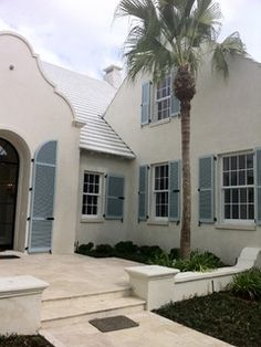 Pale Aqua Shutters On An Off White Brick House With White