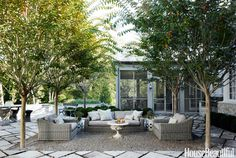 """A gravel courtyard on the back terrace defines the outdoor living room. Crape myrtles form a """"ceiling"""" over the furniture: a Provence sofa and chairs from Restoration Hardware, an antique garden urn transformed into a coffee table, and vintage ceramic garden stools. """"It's such a sheltered area, birds like to nest in the trees,"""" Whitson says. """"Sometimes it feels like you're in an aviary."""" The terrace pavers are reclaimed limestone from English sidewalks. - HouseBeautiful.com"""