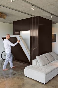"""The Cube,"" as it is known, transforms into a room, then back into a big box when closed. By lowering the custom Murphy bed and rolling a sliding plywood door, Aleksander Novak-Zemplinski creates an insta-guestroom in his small, industrial-style Warsaw loft. photos by: Andreas Meichsner"