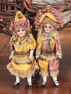 """French All Bisque Mignonettes in Original Party Costumes 5"""" (13 cm.) Each has bisque swivel head on kid-edged bisque torso,blue glass enamel inset eyes,painted lashes and brows,closed mouth,blonde mohair wig,peg-jointed bisque arms and legs,white stockings,black two lace heeled shoes. Condition: generally excellent. Comments: French,circa 1890."""
