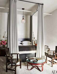 In Meg Ryan's Manhattan loft, bed curtains of a Holland & Sherry wool and a pendant light from Olde Good Things hang in the master bedroom | archdigest.com