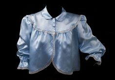 """CHAQUETILLA """"DE IR A DORMIR"""": Este tipo de prendas se utilizaban por mujeres en el siglo XIX y XX, antes de dormir o al despertar sobre el pijama o camisón, y poder moverse por la casa sin resultar indecentes o sentirse expuestas ante otros miembros familiares. Torera de Nylon azul con cuello bebé y media manga con fruncido, botones (automáticos, con falsos botones decorativos) y puntillas como remate. Producción doméstica, cosido a máquina, años 60?. Colección Mateos Olivares."""