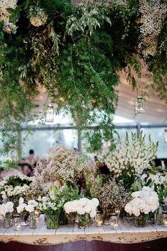 floral installation cascades down towards white floral centerpieces